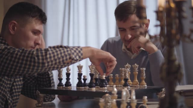Close-up of confident Caucasian men playing chess indoors. Focus changes from adult son to middle aged father. Concentrated chessmen spending evening at home. Leisure, hobby, lifestyle