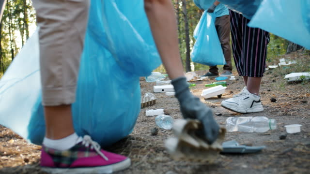 Close-up of contaminated ground in forest and activists' hands picking garbage
