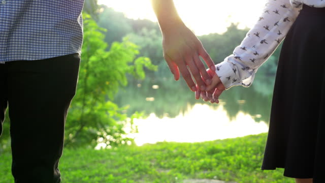 Close-up of couple holding hands at sunset and walking together video