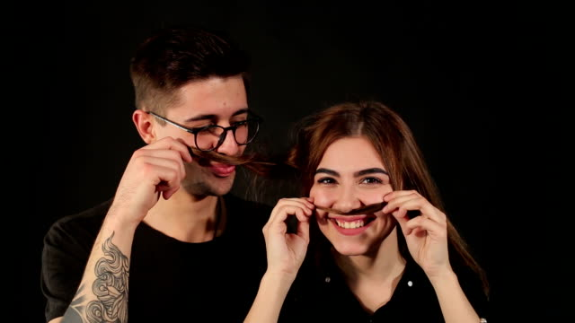 closeup of couple who makes a mustache out of hair - brunette woman eyeglasses kiss man video stock e b–roll