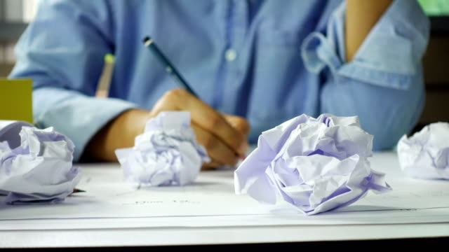 Close-up of crumpled paper on table with unhappy businesswoman was frustrated. Concept of no idea to thinking video