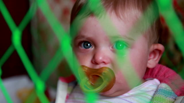 Close-up of crying baby sitting in the crib and sucking pacifier video
