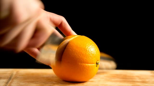 vidéos et rushes de gros plan de fruits orange coupés sur planche à découper - vue partielle