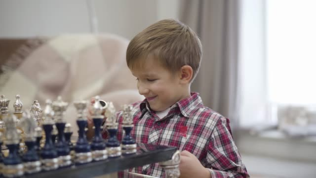 Close-up of cute Caucasian boy sitting in front of chess board and smiling. Clever child enjoying his hobby indoors. Intelligence, intellect, childhood.