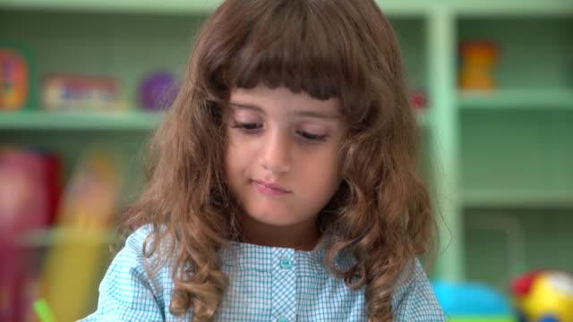 Close-up of cute preschool girl in classroom