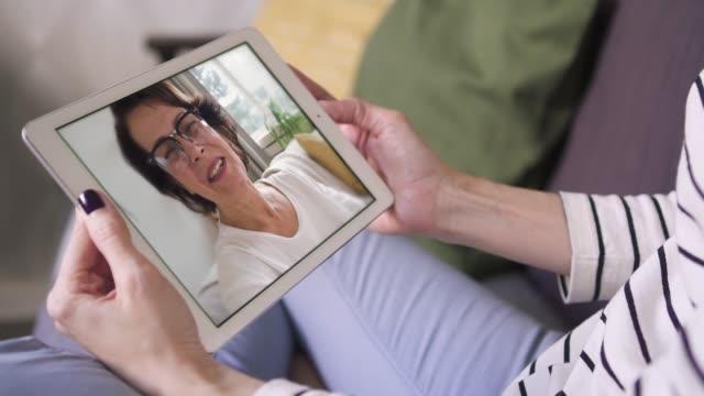 vídeos de stock, filmes e b-roll de closeup da filha que senta o anúncio que bate-se com a mamã através da chamada video com tabuleta - distante