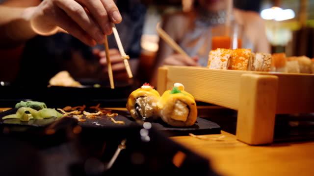 vídeos y material grabado en eventos de stock de close-up de la hija con papá y tomar el sushi palillos de madera con palos de madera en un restaurante asiático. - sushi