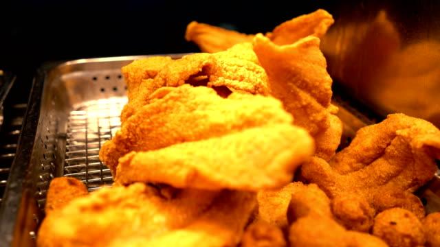 vidéos et rushes de gros plan du poisson frit délicieux & hush puppies sous warmers - aliment frit