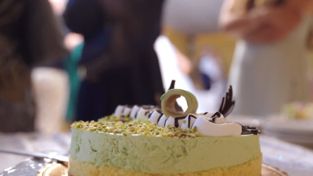 Close-up of delicious round festive cake on plate in restaurant, people standing on background. Organization and preparation of candy bar for event parties, catering banquet service concept