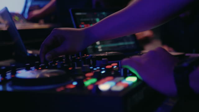closeup of dj hands mixes the track on stage in night club at party