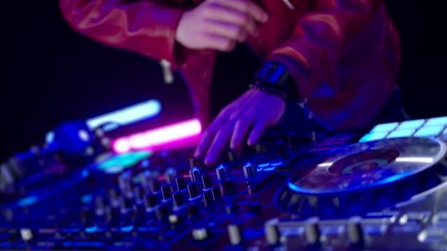 Close-Up von Dj Mixer Controller Desk in Night Club Disco Party. DJ Hands berühren Tasten und Slider Spielen elektronische Musik . Erstaunliche Nahaufnahme von DJ Hands Mixing und Scratching Musik auf Vinyl Plate – Video