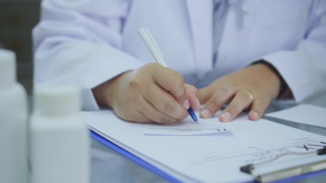 Close-up of Doctor writing a prescription at desk,Slow motion