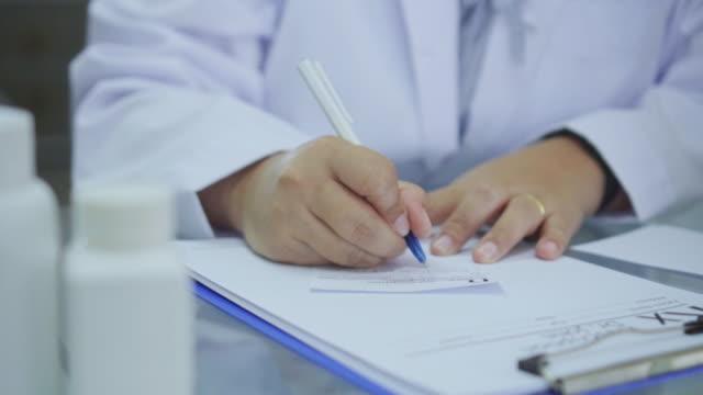 close-up of doctor writing a prescription at desk,slow motion - prescrizione medica video stock e b–roll