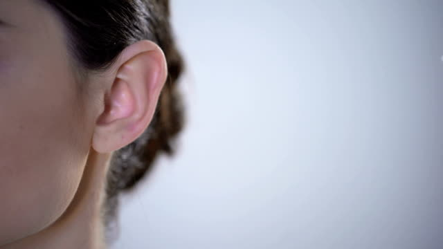closeup of ear with hearing aid, young deaf woman adjusting to environment - sordità video stock e b–roll