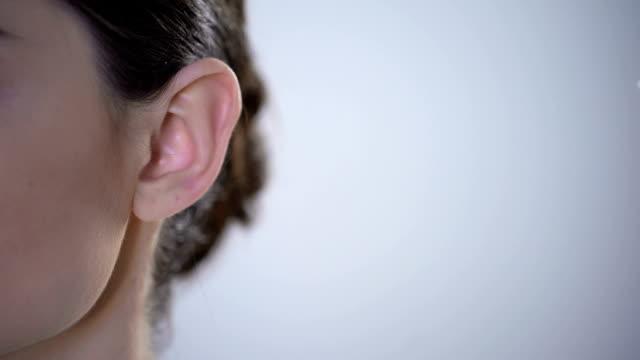 vídeos de stock, filmes e b-roll de closeup da orelha com aparelho auditivo, jovem mulher surda ajustar ao ambiente - surdo