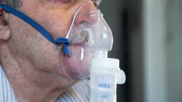 Closeup of Elderly Man Doing Inhalation Elderly Man Under Medical Treatment. He is Doing Inhalation with Nebilizer coughing stock videos & royalty-free footage