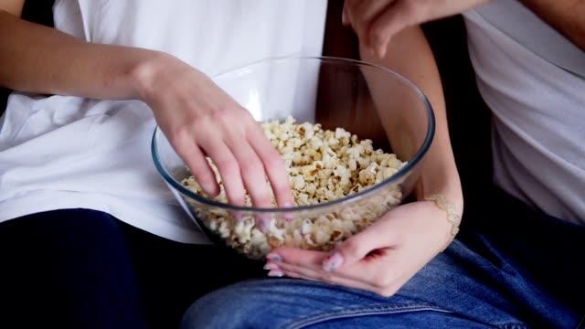 vídeos y material grabado en eventos de stock de primer plano de las manos de una pareja elegante sosteniendo un gran tazón transparente y comiendo palomitas de maíz en casa. pareja de jeans azules y camisetas blancas. sin rostro - cuenco