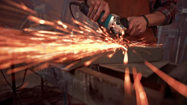 Close-up of engineer cutting metal with power tool Blacksmith working with angle grinder and cutting metal with sparks flying off in workshop blacksmith shop stock videos & royalty-free footage