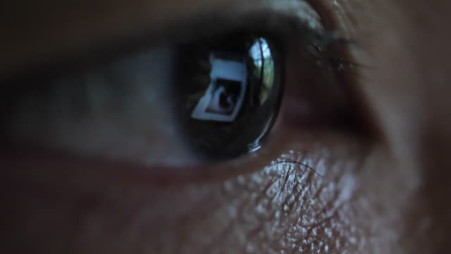 vídeos de stock e filmes b-roll de close-up of eye looking on computer monitor and smart phone - dedicação