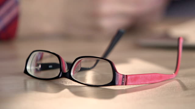 Closeup of eyeglasses on table, nice accessories for person with bad eyesight video