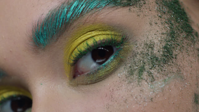 Close-up of fashion model's eyes in colorful stage make-up. Fashion video. Captured in 7K R3D Red Helium. 4K ProRes 4444. eyeshadow stock videos & royalty-free footage