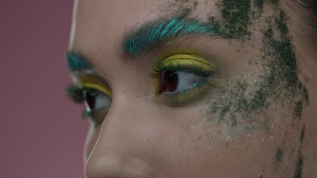 vidéos et rushes de plan rapproché des parties du visage du modèle de mode dans le maquillage coloré de scène. vidéo de mode. - fard à paupières