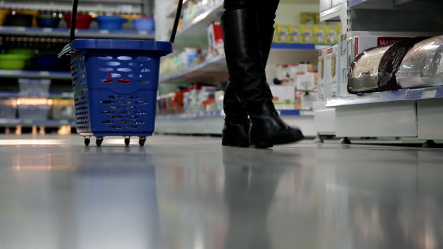 close-up of feet and girls with shopping trolley in a supermarket video