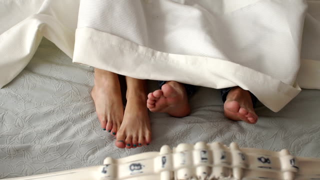 beyaz battaniyenin altında bir yatakta ayaklarıyakın çekim. - seks ve çoğalma stok videoları ve detay görüntü çekimi