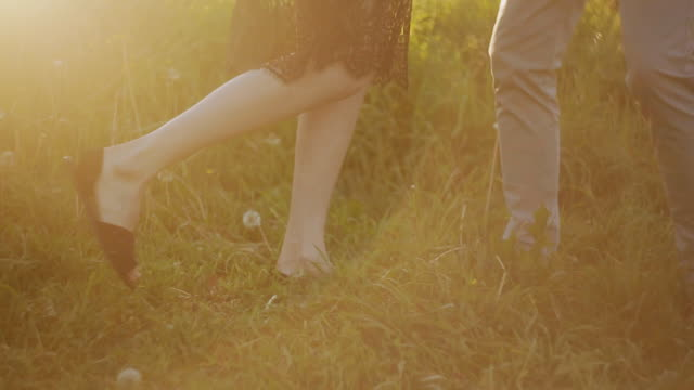 Close-up of feet of a dancing couple in love at sunset in the Park.