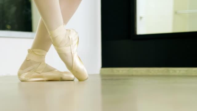 nahaufnahme der füße der balletttänzerin, die in spitzenschuhen auf zehenspitzen tanzt. 4k - ballettschuh stock-videos und b-roll-filmmaterial