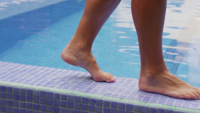 Closeup of feet walking by pool and dipping toe in water. video