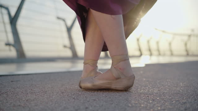 close-up of female ballet dancer feet standing up on tiptoes. unrecognizable caucasian ballerina dancing at sunrise or sunset outdoors. concept of choreography, elegance, beauty. - {{asset.href}} video stock e b–roll