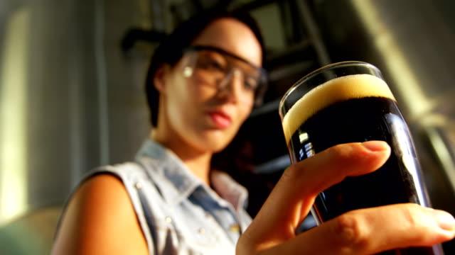 女性の醸造業者がビール 4 k のテストのクローズ アップ - 醸造所点の映像素材/bロール