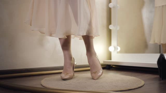 närbild av kvinnliga kaukasiska fötter i eleganta beige högklackade skor snurrar i omklädningsrummet. snygg ung oigenkännlig kvinna i snygg klänning tittar på spegel i modebutik. - klänning bildbanksvideor och videomaterial från bakom kulisserna