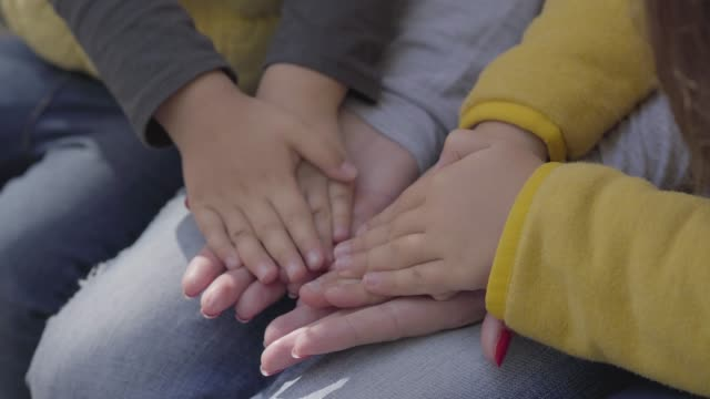 close-up of female caucasian hands holding small children's palms. kids playing with the their mother. - mano donna dita unite video stock e b–roll