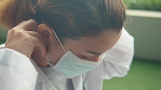 närbild av kvinnlig läkare bär kirurgisk mask för att skydda corona virus (covid-19), luta upp - face mask bildbanksvideor och videomaterial från bakom kulisserna