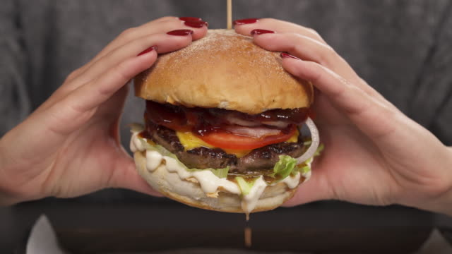 Close-up of female hand holding juicy fresh burger and squeezing it. Urban food concept
