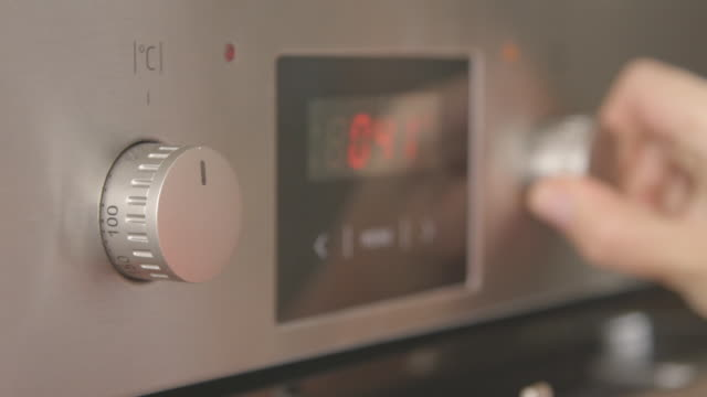 Closeup of female hand turns the oven switches sets baking mode and temperature video