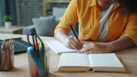 primo primo passo della scrittura a mano femminile in taccuino mentre la donna legge il libro a tavola - imparare video stock e b–roll