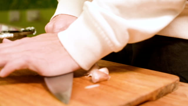 close-up of female hands at home kitchen clean garlic from the peel - aglio alliacee video stock e b–roll