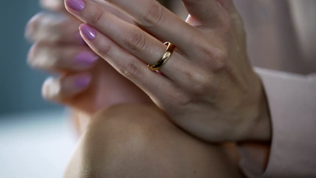 close-up of female hands lying on knees and touching gold engagement ring - ноготь на руке стоковые видео и кадры b-roll