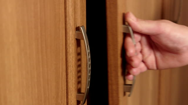 Close-up of female hands opening doors of wooden wardrobe video