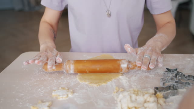 Close-up of female hands pinning dough with wooden pin cooking biscuits at home