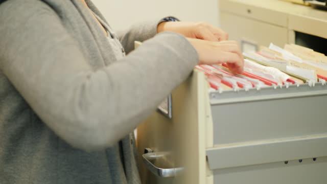 Primer plano de manos femeninas tomar una carpeta con documentos de un cajón en estilo retro. Trabajos archivados - vídeo