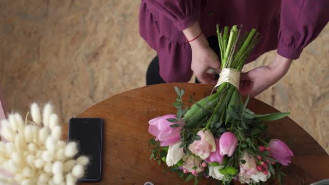 vidéos et rushes de plan rapproché des mains femelles attachées dans le ruban d'arc sur le bouquet - bouquet formel