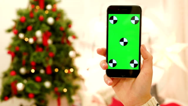 Close-up of female hands touching green screen on mobile phone. Chroma Key. Close up. Tracking motion. Vertical.with blur christmas decoration background video