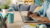 istock Close-up of female hands typing on laptop at desk at home doing freelance work 1201657341