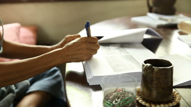 närbild av kvinnliga händer. kvinna skriva något på dokument hemma - linjerat papper bakgrund bildbanksvideor och videomaterial från bakom kulisserna