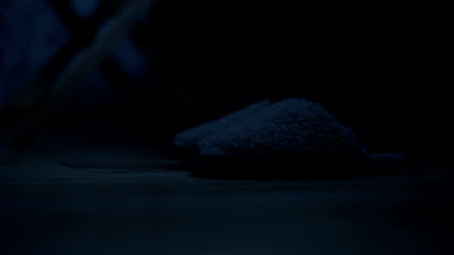close-up of female legs wearing slippers next to the bed in the bedroom. the effect of the american night. cold toning. night - pajamas stock videos & royalty-free footage