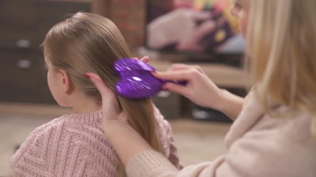 尾で女の子の髪を保持して、それを磨いて女性の手入れされた手のクローズ アップ - ブラシ点の映像素材/bロール